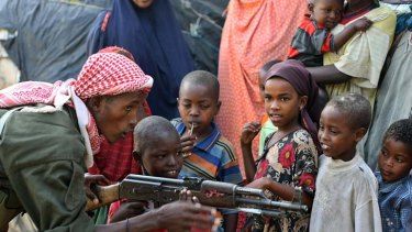 A government soldier on patrol in the streets of Somalia's war-torn capital demonstrates to Somali children how to use a Kalashnikov rifle.