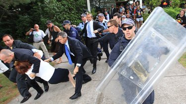 Julia Gillard is dragged away from the protest by her security officers.