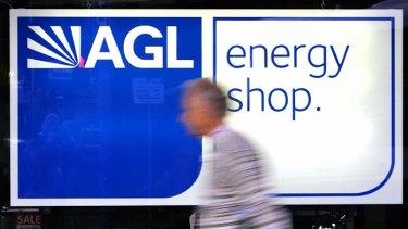 A pedestrian walks past an AGL energy sign.