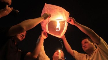People prepare to release a sky lantern during a candlelight vigil for passengers aboard a missing Malaysia Airlines plane in Kuala Lumpur, Malaysia.