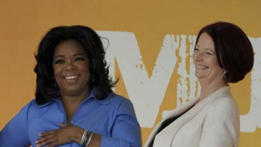 Women on top ... Oprah Winfrey and Julia Gillard share a laugh in front of screaming fans in Melbourne.