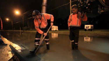 SYDNEY, AUSTRALIA - APRIL 22:  SES volunteers and contractors attempt to alleviate blocked drains on Newbridge Rd Milperra which has flooded and closed the road and access to houses in the area on April 22, 2015 in Sydney, Australia.  (Photo by James Alcock/Fairfax Media)