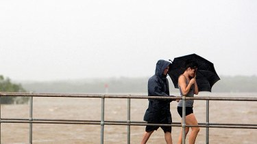 Maroochydore residents walk in torrential rain across the rising Maroochy River on January 11, 201.