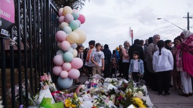 People gather for a vigil at Banksia Road Public School in Greenacre where two children where killed on Tuesday after a car unintentionally ploughed into a classroom.