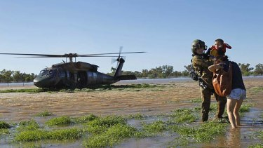 Battling the elements: An Australian soldier assists flood victims.