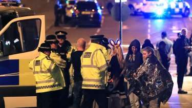 Emergency services personnel speak to people outside Manchester Arena after an explosion.