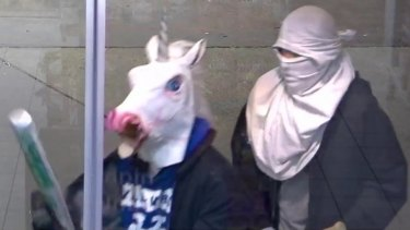 The two men, armed with baseball bats, attempt to rob a service station.