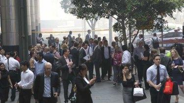 Office workers evacuate while a fire burns at Barangaroo.