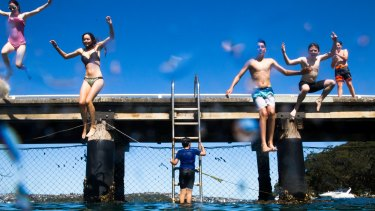 Children jump off the wharf at Chowder Bay on Sunday.