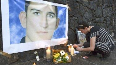 A woman lights a candle for Iranian asylum seeker Reza Berati.