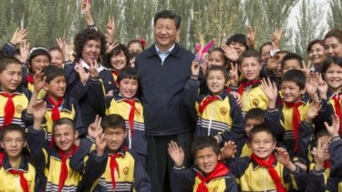 Tough response: China's President Xi Jinping, seen posing with primary school students in Shufu county, Xinjiang, on April 28, has called for decisive action against terrorist acts.