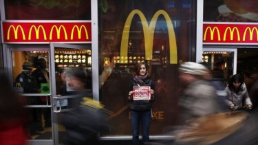 A protester holds up a poster in front of a McDonald's restaurant in Times Square, New York.
