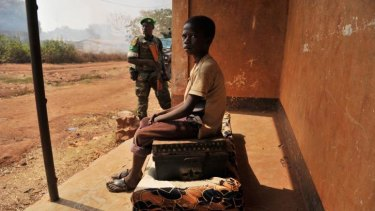 Displaced: A boy sits on the only family belongings left after an attack by Christian militias, as a member of the African Union peacekeeping force stands guard.