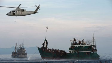 Rohingya swimming to collect food supplies dropped by a Thai army helicopter.