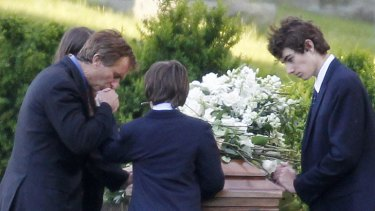 Robert F. Kennedy jnr, left, kneels with his children at the casket of Mary Kennedy, in St Francis Xavier Cemetery in Centerville, Massachusetts.