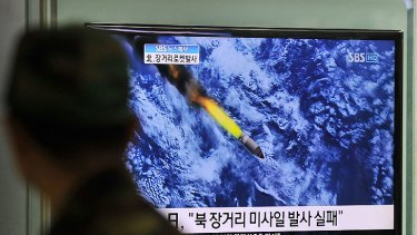 A South Korean man watches a TV screen showing a graphic of North Korea's rocket launch at a train station in Seoul.