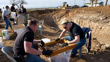 Sheriff detectives Paul Hoskins, left, and Lindsay Smith sift for human remains that were excavated from an abandoned cattle ranch.