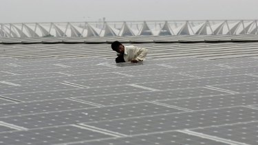 An Indian worker cleans solar panels on top of the new Thyagraj Stadium in New Delhi.