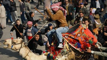 An armed  pro-government supporter rides a camel through Tahrir Square.