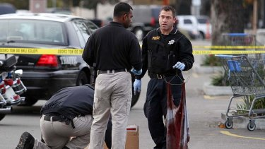A police officer holds a bloody shirt as evidence is gathered at the scene of a shooting at Wal-Mart in California.