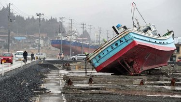 Vehicles, pictured on March 8, 2012, move among fishing vessels that were carried from Kesennuma port by the March 11, 2011 tsunami in Miyagi prefecture.