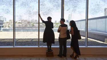 Performative drawing: Gosia Wlodarczak (left) drawing directly onto a window at the AGNSW overlooking the landscape of Woolloomooloo for the Dobell Australian Drawing Biennial 2014 at the AGNSW, with Michael Harding and Lily Lui.