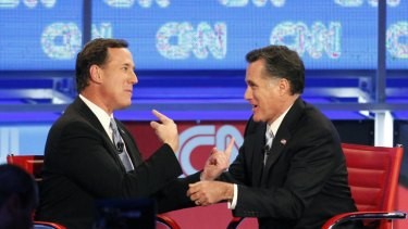 Rick Santorum (left) and Mitt Romney talk after their presidential race debate in Mesa, Arizona.
