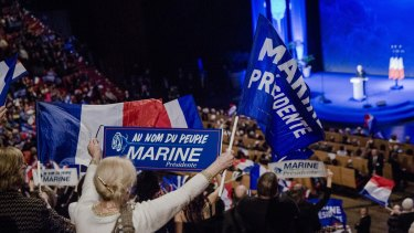 Attendees wave flags and hold signs as Marine Le Pen, leader of the French National Front, speaks in Lyon.