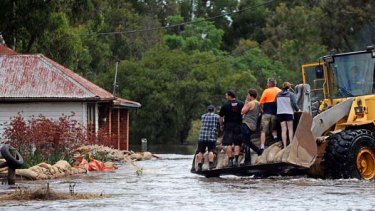 To the rescue ... residents of Skipton near Ballarat rush to sandbag a house.