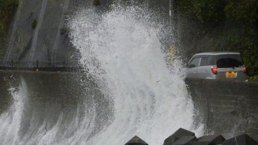A huge sea wave hit against a concrete wall to a road in Kushimoto, western Japan.