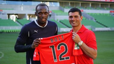 Melbourne Heart John Aloisi presents Usain Bolt with a team shirt.