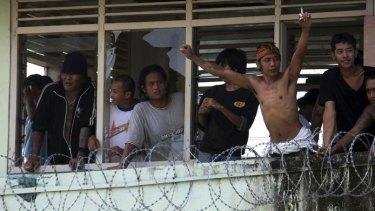 Defiant prisoners look through the broken windows of Kerobokan.
