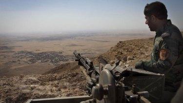 Vantage point: An Iraqi Kurdish Peshmerga fighter on the top of Mount Zardak, a strategic point about 25 kilometres east of Mosul taken on September 6.