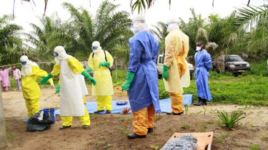 The wrapped remains of a new born child suspected of contracting the Ebola virus, lays on a stretcher as health workers,  move the body for burial in Dubreka, Guinea last week.