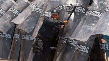 Bringing down barriers … an instructor pushes on the shields of riot police training to provide security for the G20 leaders' summit in the Mexican resort of Los Cabos.