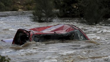 A four-wheel-drive vehicle in Paddys River upstream from the Cotter Reserve in the ACT. The driver died after trying to cross the raging torrent.