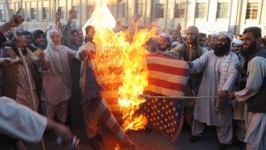 Demonstrators set fire to a US flag.
