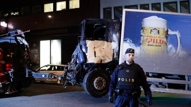 A destroyed truck is pulled away by a service car after it was driven into a department store in Stockholm.