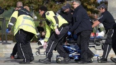 Paramedics and police rush Corporal  Nathan Cirillo for emergency treatment, to no avail.