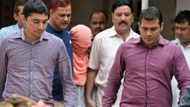Indian policemen escort the juvenile in pink hood, accused in the December 2012 gang-rape of a student, following his guilty verdict at a court in Delhi.
