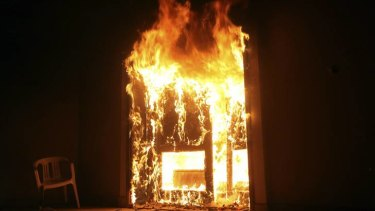 American killed ... the US Consulate in Benghazi in flames during a protest by an armed group.
