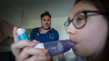 Asthma sufferer Angelique Harkins uses a spacer with her puffer, overseen by Dr Mark Hotu.