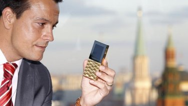 Mathias Rajani, Aesir's chief commercial officer, holds a model of his company's new mobile phone during a press presentation in Moscow.