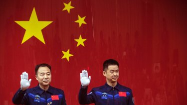 Chinese astronauts Jing Haipeng, left, and Chen Dong, right, wave from behind a glass enclosure during at the Jiuquan Satellite Launch Center in northwest China.