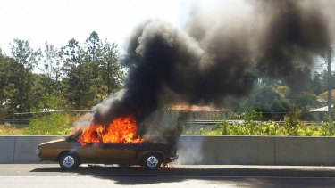 A Holden Kingswood catches fire on the Ipswich Motorway.