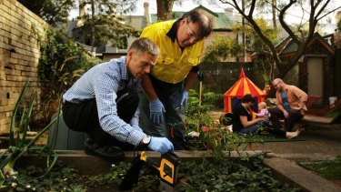 Dirty bomb: Mark Taylor and Damian Gore test the soil in the backyard of Tilly Boleyn and Rick Calder (in background with infant daughter Saskia) for lead levels.