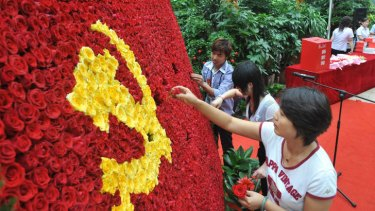 Blossoming street cred ... Chinese volunteers arrange a bed of flowers in a form of the flag of the Chinese Communist Party last year.