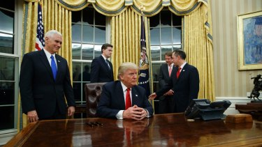 Vice President Mike Pence (left) watches as President Donald Trump prepares to sign his first executive order.