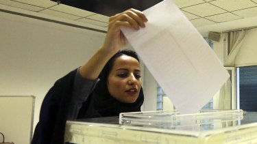A Saudi woman votes in municipal elections in December 2015, the first where women voted and ran for election. Despite progress in gaining the franchise, women are still subject to laws that make men their guardians for basic personal decisions.