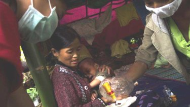 A mother and child receive medical aid in a jungle in the far north of Burma, where soldiers have been fighting rebels since a 17-year ceasefire ended in June.
